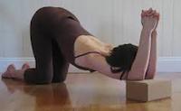 À genoux épaules reposées sur une brique